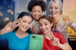 Szczęśliwe młode kobiety bierze selfie z smartphone Zdjęcie Royalty Free