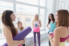 Szczęśliwe młode kobiety gawędzi przed ich joga klasą zdjęcie royalty free