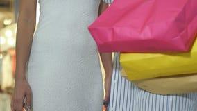 Szczęśliwe młode kobiety opowiada w centrum handlowym z smartphones i torba na zakupy zbiory