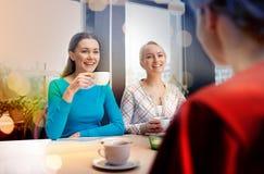 Szczęśliwe młode kobiety pije herbaty lub kawy przy kawiarnią Zdjęcia Stock