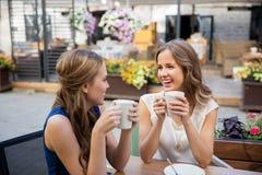 Szczęśliwe młode kobiety pije kawę przy plenerową kawiarnią Zdjęcie Royalty Free