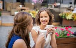Szczęśliwe młode kobiety pije kawę przy plenerową kawiarnią Zdjęcie Stock