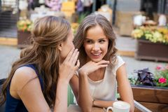 Szczęśliwe młode kobiety pije kawę przy plenerową kawiarnią Obraz Royalty Free
