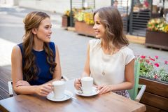Szczęśliwe młode kobiety pije kawę przy plenerową kawiarnią Obraz Stock