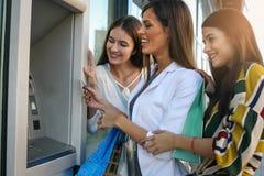 Szczęśliwe młode kobiety używa gotówkową maszynę Kobiety używa kredytową kartę Fotografia Royalty Free