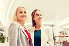 Szczęśliwe młode kobiety w centrum handlowym lub centrum biznesu zdjęcie stock