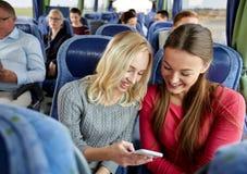 Szczęśliwe młode kobiety w podróż autobusie z smartphone Zdjęcia Stock