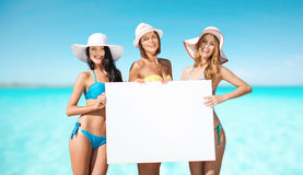 Szczęśliwe młode kobiety z białą deską na lecie wyrzucać na brzeg Fotografia Royalty Free