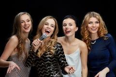 Szczęśliwe młode kobiety z mikrofonu śpiewackim karaoke Obrazy Royalty Free