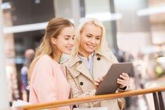 Szczęśliwe młode kobiety z pastylek torba na zakupy i komputerem osobistym obraz stock