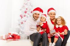 Szczęśliwe młode rodzinne otwarcie teraźniejszość na bożych narodzeniach Zdjęcie Royalty Free