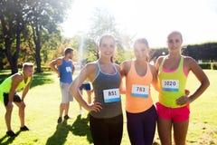 Szczęśliwe młode sporty kobiety z bieżnymi odznak liczbami Fotografia Royalty Free