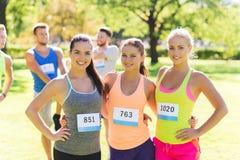 Szczęśliwe młode sporty kobiety z bieżnymi odznak liczbami Obrazy Royalty Free