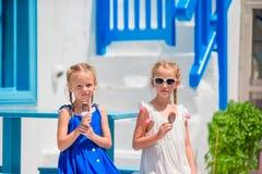 Szczęśliwe małe dziewczynki je lody w openair kawiarni w starej ulicie Zdjęcie Stock