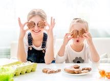 Szczęśliwe małe dziewczynki trzyma Wielkanocnych ciastka przed ich oczami Obrazy Stock
