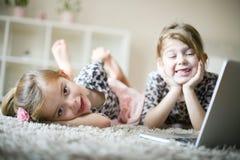 Szczęśliwe małe dziewczynki używa laptop obraz stock