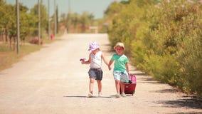 Szczęśliwe małej dziewczynki i chłopiec mienia ręki, iść na drodze zbiory