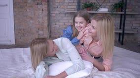 Szczęśliwe macierzyństwo, wesoła kobieta komunikuje się z pięknymi dorosłymi i małymi córkami leżącymi na łóżku, relaksując się w zbiory