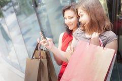 Szczęśliwe mod kobiety z torbami używać telefon komórkowego, centrum handlowe Obrazy Stock