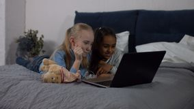 Szczęśliwe multiracial dziewczyny cieszy się kreskówki na laptopie zbiory
