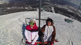 Szczęśliwe narciarki iść up w narciarskim dźwignięciu góra przy słonecznym dniem zdjęcie wideo