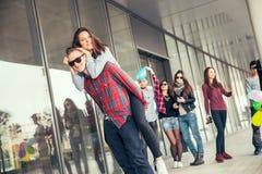 Szczęśliwe nastoletnie dziewczyny i chłopiec ma dobrą zabawę synchronizują outdoors Zdjęcia Royalty Free
