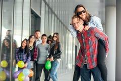 Szczęśliwe nastoletnie dziewczyny i chłopiec ma dobrą zabawę synchronizują outdoors Zdjęcie Royalty Free