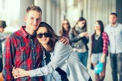 Szczęśliwe nastoletnie dziewczyny i chłopiec ma dobrą zabawę synchronizują outdoors Obraz Royalty Free