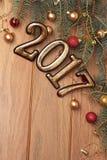 Szczęśliwe nowego roku złota 2017 postacie na drewnianym tle z Bożenarodzeniowymi dekoracjami zamykają, piłki i prezenty Fotografia Stock