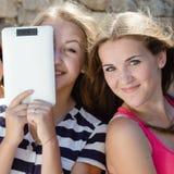 Szczęśliwe ono uśmiecha się ładne dziewczyny i pastylka komputer fotografia royalty free