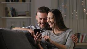 Szczęśliwe pary udzielenia słuchawki ogląda wideo zdjęcie wideo