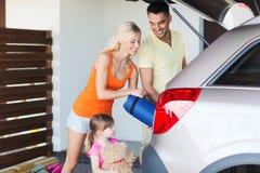 Szczęśliwe rodzinne kocowanie rzeczy samochód parkuje w domu Fotografia Stock