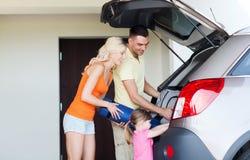 Szczęśliwe rodzinne kocowanie rzeczy samochód parkuje w domu Zdjęcia Stock
