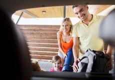 Szczęśliwe rodzinne kocowanie rzeczy samochód parkuje w domu Obrazy Royalty Free