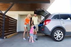 Szczęśliwe rodzinne kocowanie rzeczy samochód parkuje w domu Obraz Royalty Free