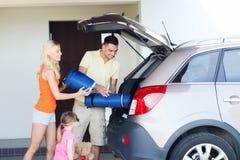 Szczęśliwe rodzinne kocowanie rzeczy samochód parkuje w domu Fotografia Royalty Free