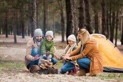 szczęśliwe rodzinne nagrzanie ręki z ogniskiem podczas gdy zdjęcie stock