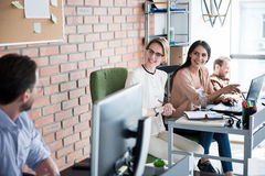 Szczęśliwe uśmiechnięte kobiety siedzi blisko biurka fotografia royalty free