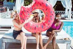 Szczęśliwe wieloetniczne kobiety pozuje z nadmuchiwanym pączkiem blisko pływackiego basenu obrazy stock