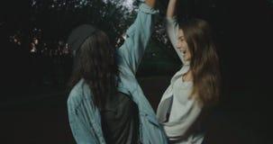Szczęśliwe wielokulturowe modniś dziewczyny tanczą, wirują round i ściskają podczas ich spaceru w wieczór, zbiory