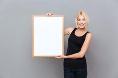 Szczęśliwego ładnego młodej kobiety mienia pusta biała deska Zdjęcie Royalty Free