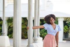 Szczęśliwego afro amerykańskiego kobiety mienia szpaltowy patrzeć daleko od Zdjęcie Royalty Free