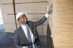 Szczęśliwego amerykanina afrykańskiego pochodzenia męski kontrahent sprawdza drewniane deski podczas gdy trzymający pastylka pecet Zdjęcie Stock