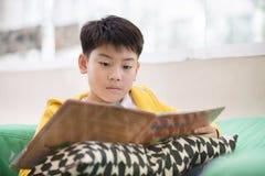 Szczęśliwego azjatykciego dziecka czytelnicza książka z uśmiech twarzą Fotografia Royalty Free