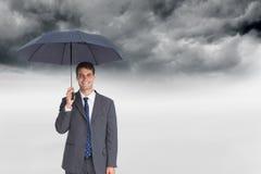 Szczęśliwego biznesmena mienia popielaty parasol Obrazy Royalty Free