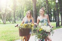 Szczęśliwego boho modne dziewczyny jadą wpólnie na bicyklach w parku Obraz Royalty Free