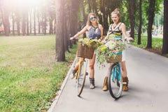 Szczęśliwego boho modne dziewczyny jadą wpólnie na bicyklach w parku Obrazy Stock