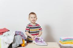 Szczęśliwego chłopiec prasowania rodzinna odzież na prasowanie desce z żelazem Dzieciak pomaga z sprzątaniem na białym tle obraz stock