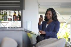 Szczęśliwego czarnego afrykanina amerykańska kobieta pracuje od restauraci prętowy texting na interneta telefonie komórkowym Obraz Stock