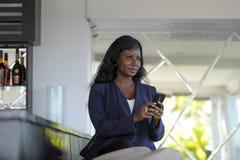 Szczęśliwego czarnego afrykanina amerykańska kobieta pracuje od restauraci prętowy texting na interneta telefonie komórkowym Obraz Royalty Free